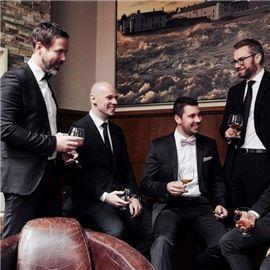 Five men in black suits drinking wine